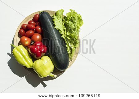 Fresh summer vegetables harvest from garden. Top view on multiple kinds of vegetables in bowl lying on white wooden table.