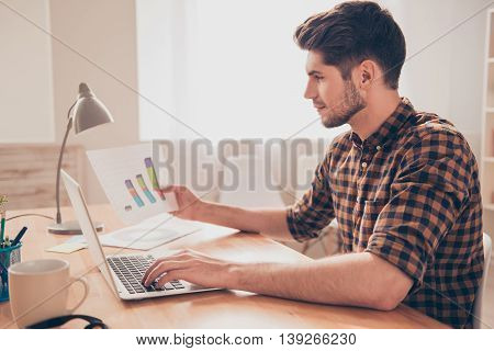 Side View Of Concentrated Young Man Working With Laptop And Diagrama
