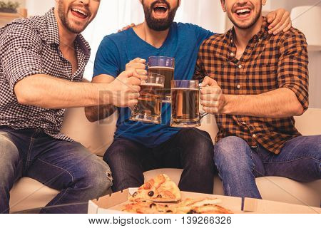 Cheers! Close Up Photo Of Handsome Men Celebrating Victory And Clinking Glass Of Beer