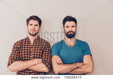 two handsome serious men cross hands while standing gray background
