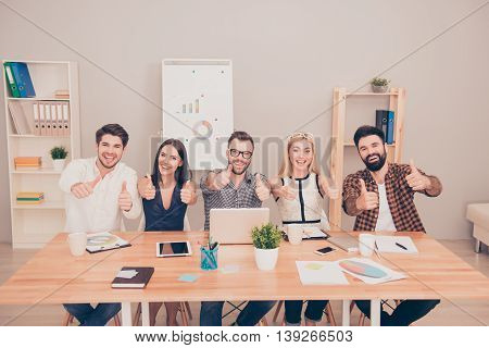 Photo Of  Happy Young Team Sitting At Conference Table Smiling And Thumb Up