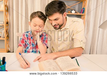 Schoolboy Doing Hometask With Father And Writting In Workbook