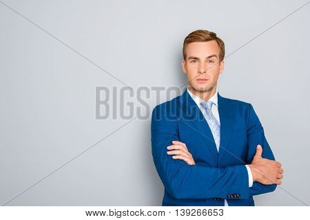 Confident Successful Businessman With Crossed Hands On Gray Background