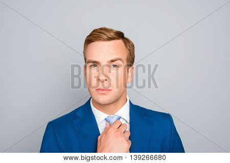 Portrait Of Handsome Businessman In Blue Suit Correcting His Tie