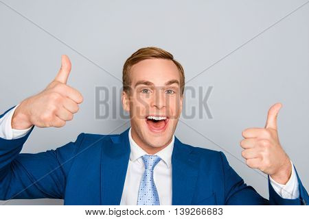 Cheerful Happy Man In Blue Suit  Showing Thumbs Up
