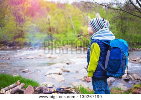 A little boy with a backpack standing on the banks of the river.