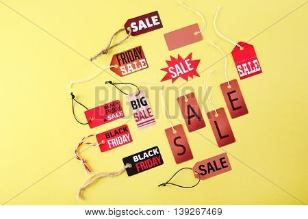 Paper tags with strings and word sale on yellow background