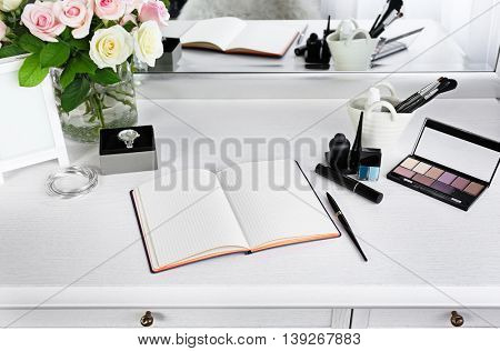 Cosmetic and notebook on light dressing table