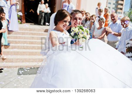 Groom Holding Bride On Hands After Church Registration