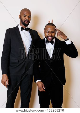 two afro-american businessmen in black suits emotional posing, gesturing, smiling. wearing bow-ties close up