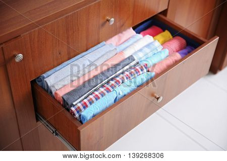 Neatly folded clothes in wooden drawer