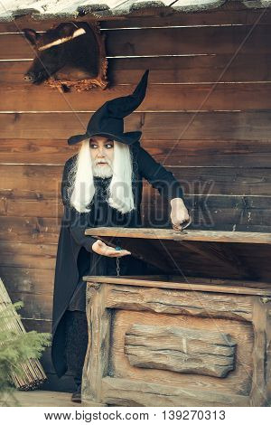 Old man wizard with long grey hair beard in black costume and hat for Halloween standing near wooden chest or trunk box on log house background