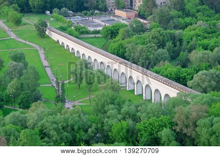 People walk in green park near Rostokino aqueduct in Moscow, Russia