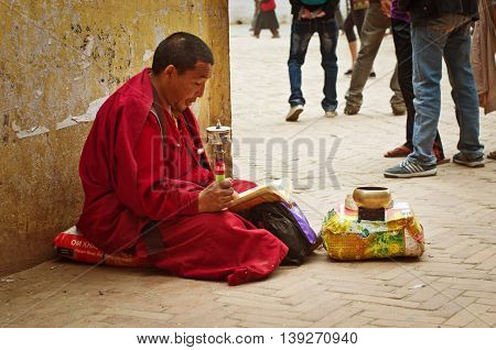 KATHMANDU NEPAL - CIRCA APR : Tibetan monk near Bodhnath stupa on Apr 2014 in Kathmandu. Bodhnath stupa is center of Buddhism pilgrimage in Nepal.
