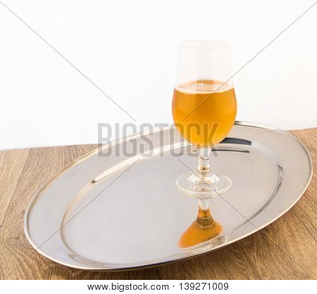 Glass of beer on the silver tray. Light background