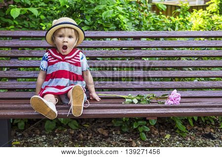 Cute little girl yawning while sitting on the bench