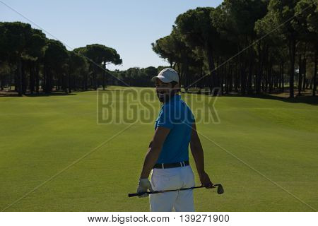 handsome middle eastern golf player portrait from back with course in background  at beautiful sunny day