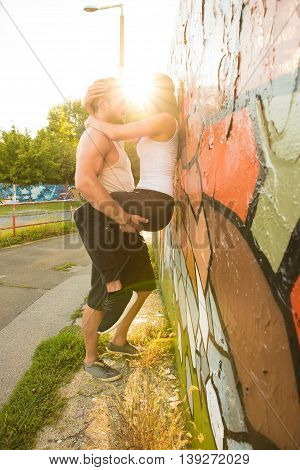 A young male holding the girl at the wall during sunset in a urban environment.