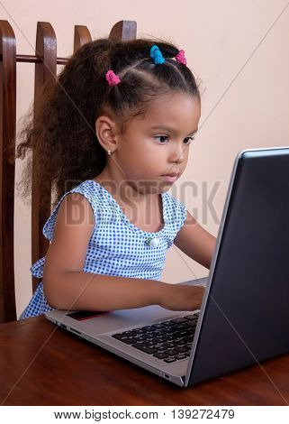Cute small multiracial girl working on a laptop computer