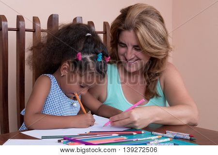 Cute multiracial small girl and her mother drawing with color pencils
