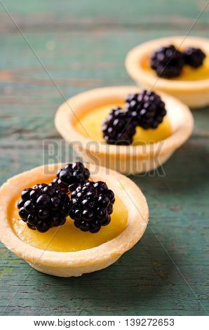 Homemade round tartlets with lemon curd and fresh blackberries on wooden table