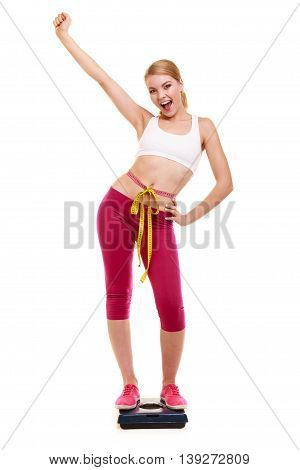 Woman Measuring On Weighing Scale With Raised Arm.