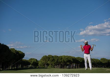 handsome middle eastern golf player portrait at course at sunny day wearing red  shirt