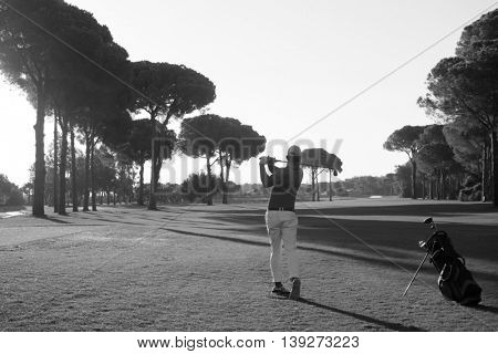 handsome sporty man, golf player hitting shot with club on course at beautiful morning