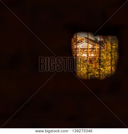 Real view of the old church through the vintage small window in the abandoned medieval house. For background, with empty space for your message, square. Photoart