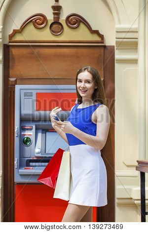 Young happy brunette woman withdrawing money from credit card at ATM, indoor shop
