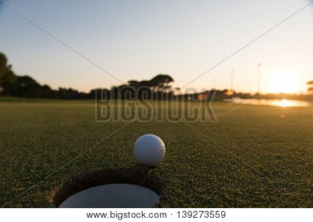 golf ball on edge of course hole representing achivement and success business concept, beautiful sunset in background