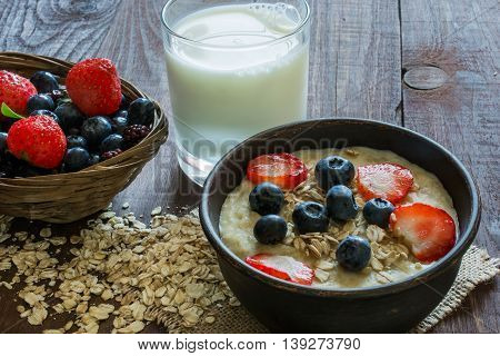 Oatmeal porridge with berries and glass of milk on wooden table, close up view. healthy breakfast