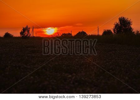 Scenic view of red and golden sunset in cloudy day in the village