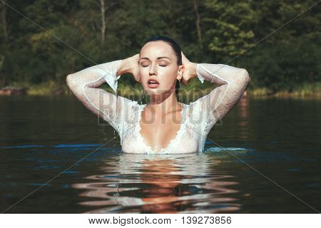woman emerged from the water she is wearing a white dress drops dripping from her face