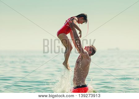 Little girl child and father having fun in ocean. Kid and man bathing in sea water. Summer vacation holiday relax.