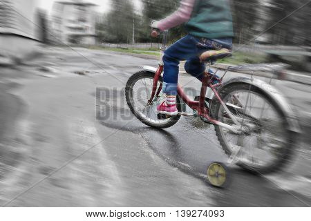 Child dangerous moves on a bicycle on the roadway.