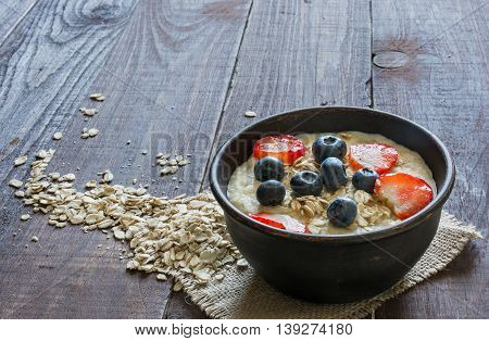 healthy homemade oatmeal porridge with berries and oat flakes in a pottery bowl on canvas for breakfast