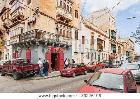 FLORIANA MALTA - February 20 2010. Street life in Malta. A group of men gathered around the bar.