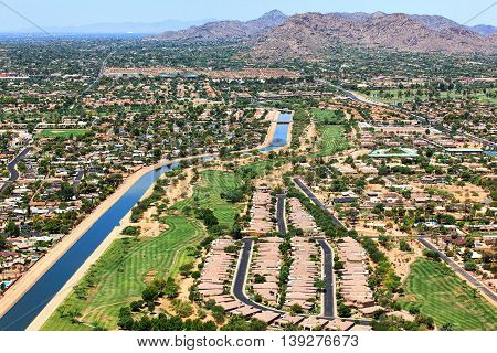 Aerial view of golf course along canal with in residential desert setting