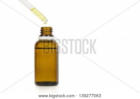 Pouring drops in a medicine bottle, over a white background.