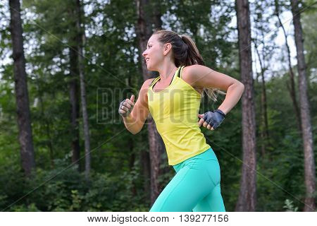 Female runner training outdoor in profile. Healthy lifestyle image of young woman jogging outside