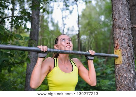 Fit woman training pull ups on horizontal bar in city park outdoors.