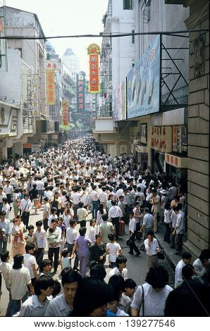 GUANGZHOU / CHINA - CIRCA 1987: Large numbers of people crowd the streets of Guangzhou.