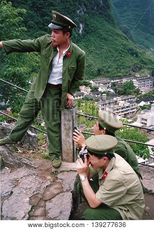 YANGSHUO / CHINA - CIRCA 1987: Chinese soldiers on leave enjoy the mountainous scenery and take photographs around Yangshuo.