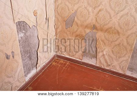 Carrying out repair work, the replacement of old paper wallpaper, renovation of residential apartments, building debris, cracked concrete wall, housing a terrible state