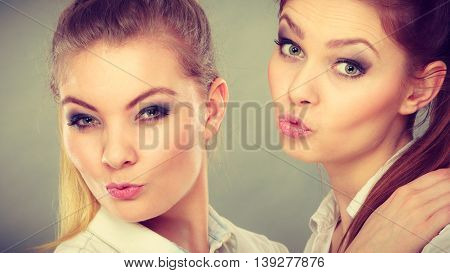 Family and relations. Love and affection concept. Two lovely attractive women playing together. Charming playful sisters have fun smiling. Girls blowing kiss.