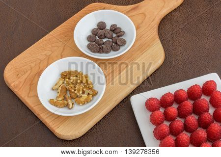 Red raspberries, walnuts, and chocolate chips laid out to make a tasty treat