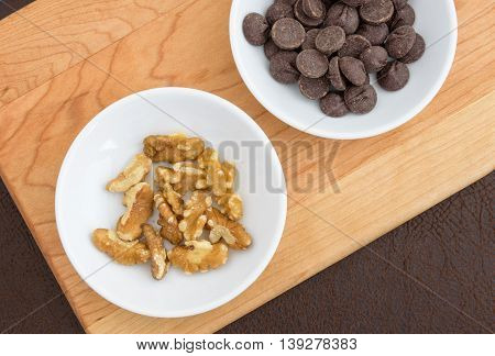 Walnuts, and chocolate chips laid out on a cutting board to make a tasty treat
