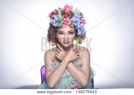 Studio Shot Of A Good Looking Young Woman Wearing White Attire And A Crown Of Faux Flowers On Her He