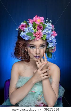 Studio shot of a good looking young woman wearing white attire and a crown of faux flowers on her head.